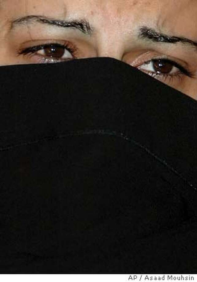 A woman who claims that she was raped by three members if the Iraqi police force cries as she talks to members of the press in Baghdad, Iraq, Monday, Feb. 19, 2007. Prime Minister Nouri al-Maliki ordered an investigation Monday into allegations by a Sunni Arab woman that she was raped by three members of the Shiite-dominated police force after she was detained over the weekend. (AP Photo/Asaad Mouhsin) Photo: ASAAD MOUHSIN