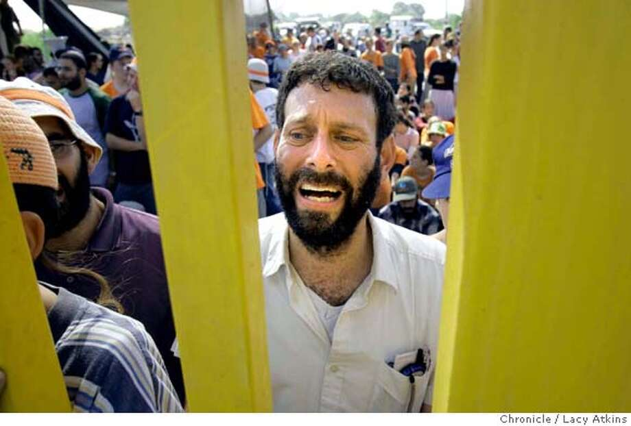 Shlomo Drazin a resident of Gadid cries at the front gate as he anothers block the entrance to keep the IDF from being able to come inside the settlement to serve the disengagement papers, Aug. 15, 2005, in Gush Katiff.  Zipi Ben-Sadon, mother , Yonatan oldest boy, Avsha lom,soldier, Neta, daughter, Nadav, youngest child. A family in a settlement in Gush Katif which is expected to be moved in the disengagement .. Photographer Lacy Atkins Photo: Lacy Atkins