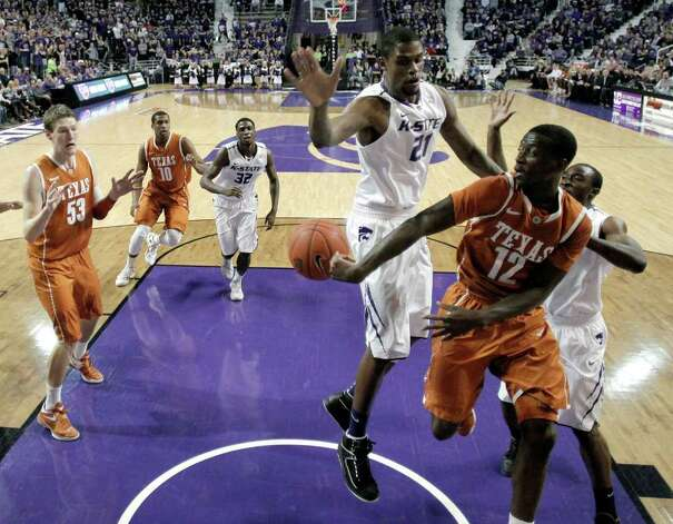 Texas guard Myck Kabongo (12) passes the ball to keep if from going out of bounds as he is pressured by Kansas State center Jordan Henriquez (21) during the first half of an NCAA college basketball game on Wednesday, Jan. 18, 2012, in Manhattan, Kan. Photo: AP