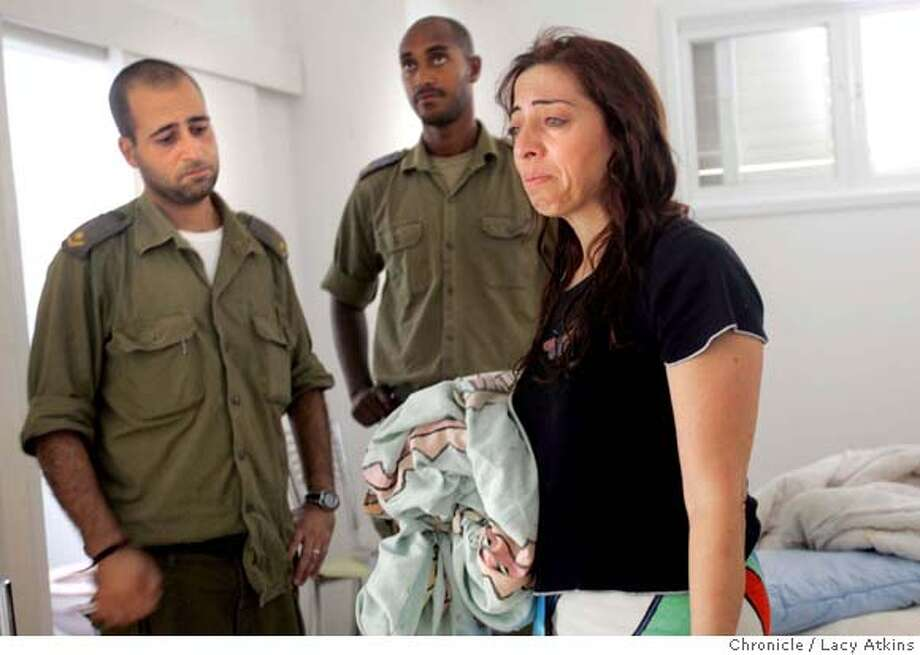 Zipi Ben-Sa'adon cries as she talks to the soldiers about the thirty plus years she has lived in her home in Gadid and now is being disengaged from Gush Katiff. and family move from Gadid settlement in Gush Katiff. Zipi Ben-Sadon, mother , Yonatan oldest boy, Avsha lom,soldier, Neta, daughter, Nadav, youngest child. A family in a settlement in Gush Katif which is expected to be moved in the disengagement .. Photographer Lacy Atkins Photo: Lacy Atkins