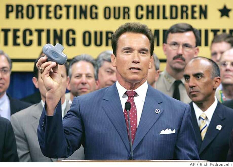 Gov.Arnold Schwarzenegger displays a global positioning device that registered would have to wear for the rest of their lives if convicted under a proposed law that he is supporting, at a Capitol news conference held in Sacramento,Calif., Tuesday, Aug. 16,2005. If passed, the legislation proposed by state Sen. George Runner, R-Antelope Valley, and his wife, Assemblywoman Sharon Runner, R-Antelope Valley, would among other things, stregthen punishments, expand parole periods, keep away from schools and places where children frequent, along with tracking of conviceted .(AP photo/Rich Pedroncelli) Photo: RICH PEDRONCELLI