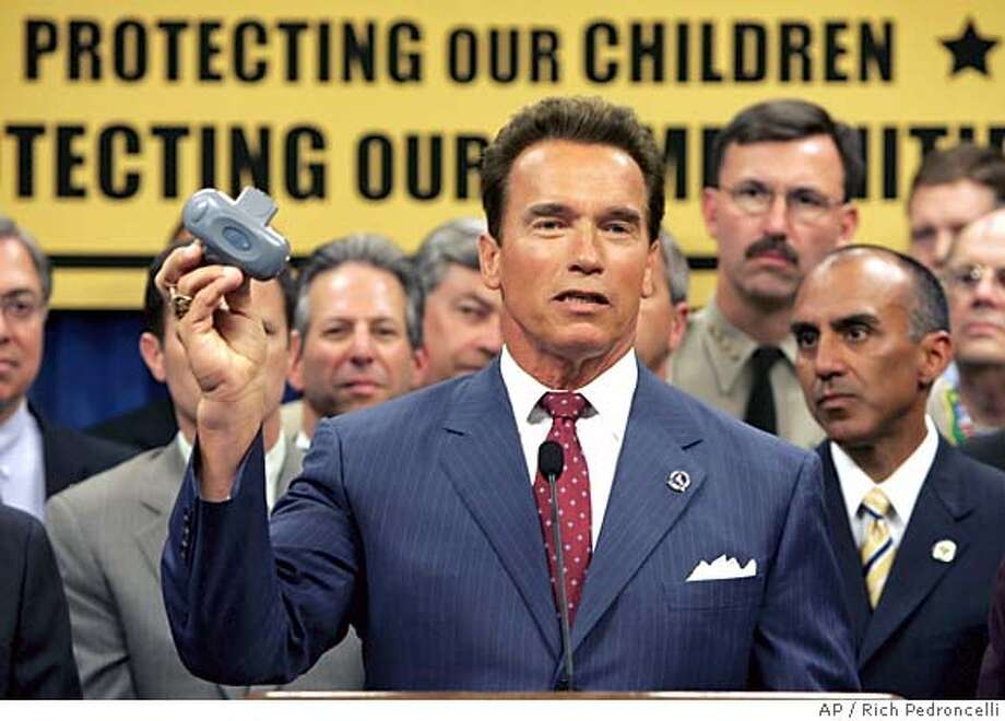 Gov. Arnold Schwarzenegger displays a global positioning device during a Capitol news conference in Sacramento, Calif., Tuesday, Aug. 16, 2005. Schwarzenegger has proposed sweeping new penalties on sex offenders, including a requirement that paroled violators wear satellite monitors for life. (AP Photo/Rich Pedroncelli) Photo: RICH PEDRONCELLI