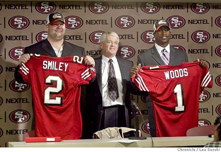 San Francisco 49ers coach Dennis Erickson, center, is flanked by draft picks Justin Smiley of Alabama, left, and Rashaun Woods of Oklahoma, Sunday, April 25, 2004, during a news conference at 49ers headquarters in Santa Clara, Calif. (AP Photo/The San Francisco Chronicle, Lea Suzuki) Ran on: 07-29-2004  Coach Dennis Erickson (center) will enter training camp without Justin Smiley (left) and Rashaun Woods in the fold. Ran on: 07-29-2004  Coach Dennis Erickson (center) will enter training camp without Justin Smiley (left) and Rashaun Woods in the fold. MANDATORY CREDIT FOR PHOTOG AND SF CHRONICLE, , MAGS OUT Photo: LEA SUZUKI