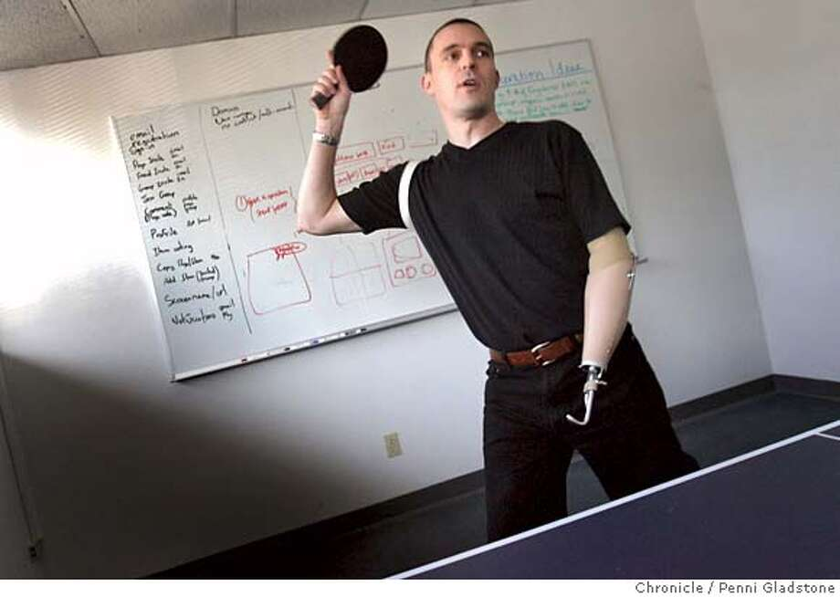 ONEHAND McCammon shows off his ping pong skills with a workmate at the office.  Keiron McCammon, the 35-year-old cofounder of Kabooble, an Internet company, was paragliding in Columbia when he hit power lines, badly burning his left hand. Many surgeries could not save his hand and he had to have the hand amputated. Despite months of recovery, he's back at work fulltime.  Event on 12/5/06 in Santa Clara.  Penni Gladstone / The Chronicle MANDATORY CREDIT FOR PHOTOG AND SF CHRONICLE/NO SALES-MAGS OUT Photo: Penni Gladstone