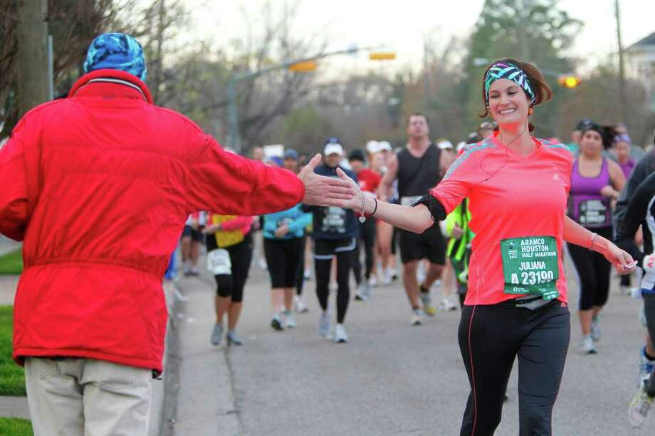 Juliana Uribe high-fives a spectator along Michaux near the 5-mile mark during the Aramco Houston Half Marathon on Sunday. Spectators and volunteers received high marks this year from runners. Photo: Mayra Beltran / © 2011 Houston Chronicle
