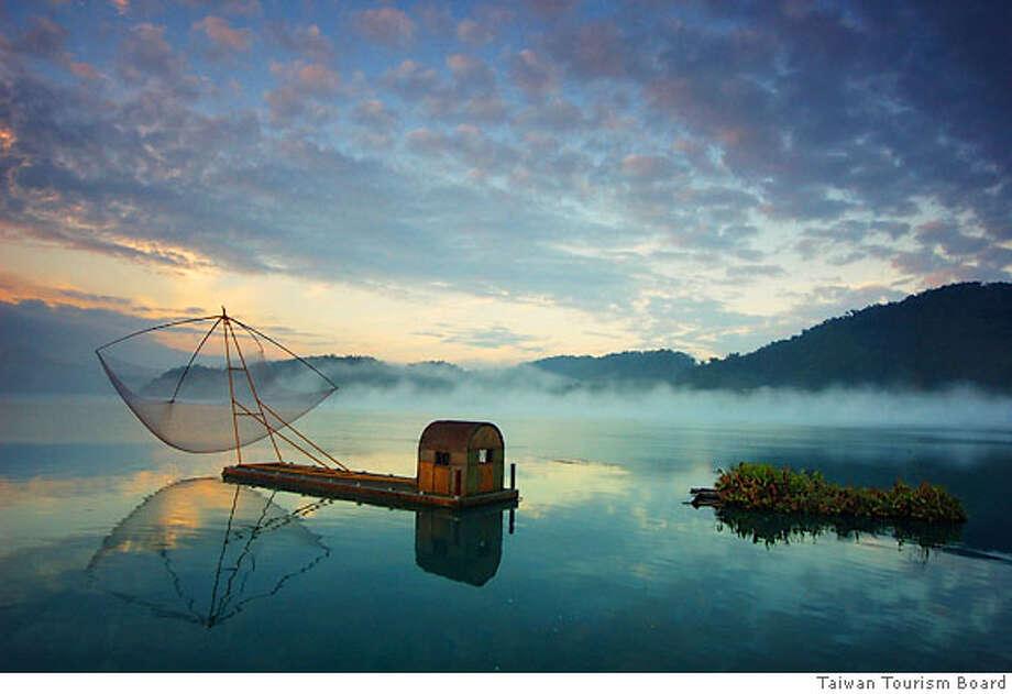 TRAVEL TAIWAN -- A fishing raft floats on ethereal Sun Moon Lake in Taiwan.  credit: Taiwan Tourism Board Photo: Taiwan Tourism Board