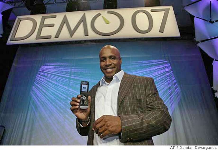 San Francisco Giants slugger Barry Bonds demonstrates Bling Software Inc. platform technology on his cellphone at the DEMO technology show in Palm Desert, Calif., Wednesday, Jan. 31, 2007. Bling Software uses a programming technique called Ajax to deliver Web-like modules of content to any phone with a browser, on any wireless carrier's network. (AP Photo/Damian Dovarganes) Photo: Damian Dovarganes