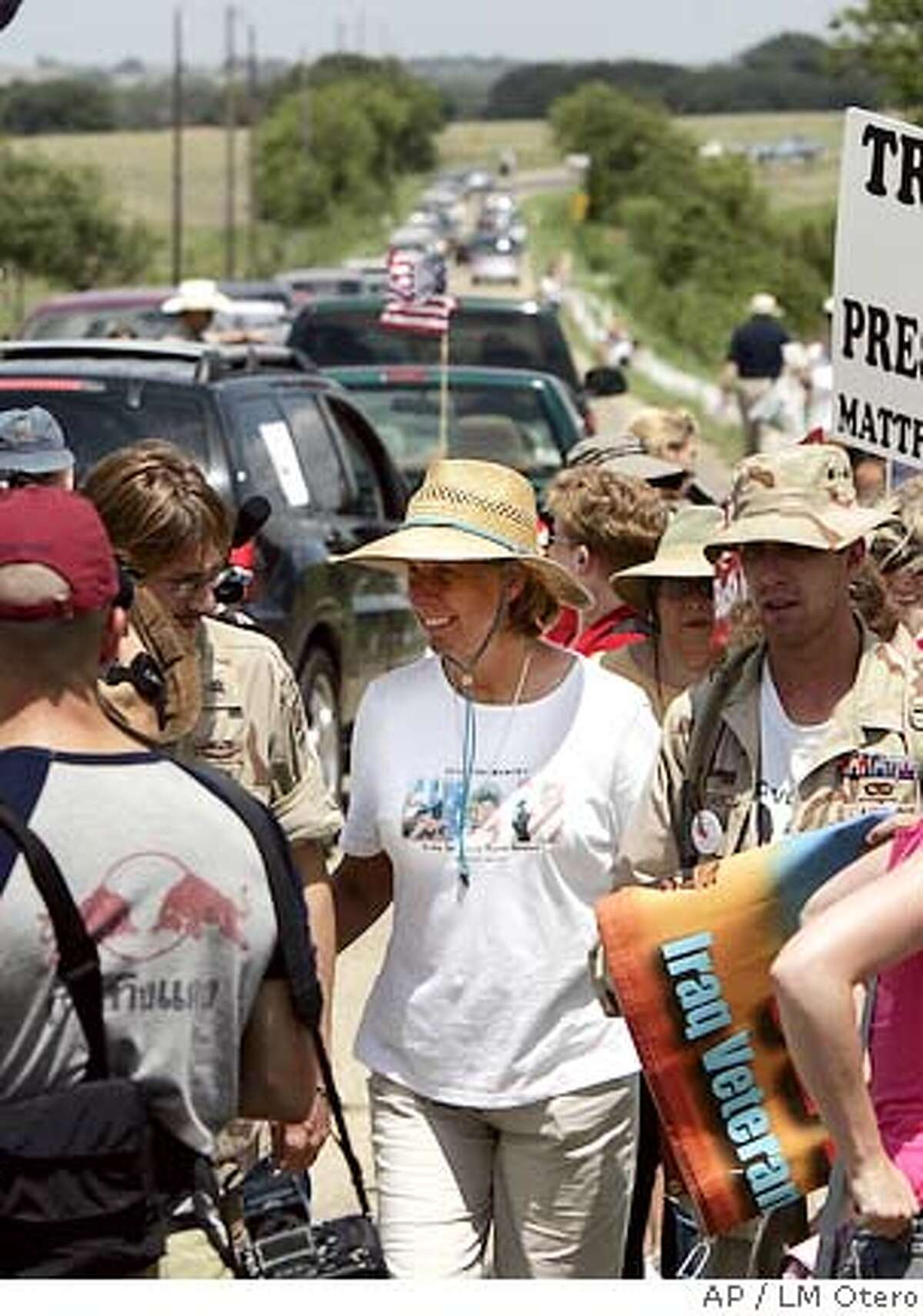 Cindy Sheehan, center, walks with supporter as dozens of cars drive on the road leading to President Bush's ranch near Crawford, Texas, Saturday, Aug. 13, 2005. A grieving mother's anti-war protest entered its second week, gaining momentum and spurring counter rallies, as hundreds of people with conflicting opinions about the war in Iraq descended Saturday on a road leading to the Western White House. (AP Photo/LM Otero)