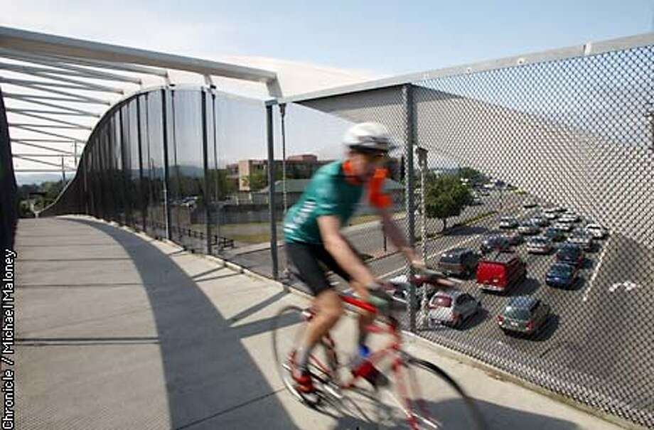 A cyclist pedals over traffic on Ygnacio Valley Road in Walnut Creek. The Iron Horse Trail overcrossing was dedicated in May, 1998.  Advance for Bike to Work Day. Story will focus on the variety of bike lanes, trails and facilities that have been built in the last several years to accomodate bicyclists, whether commuters or recreational users.  Assignment is to photograph somebody using the Iron Horse Trail in Contra Costa County, one of the region's most extensive and popular trails. Event on 5/14/03 in Concord. MICHAEL MALONEY / The Chronicle Photo: MICHAEL MALONEY