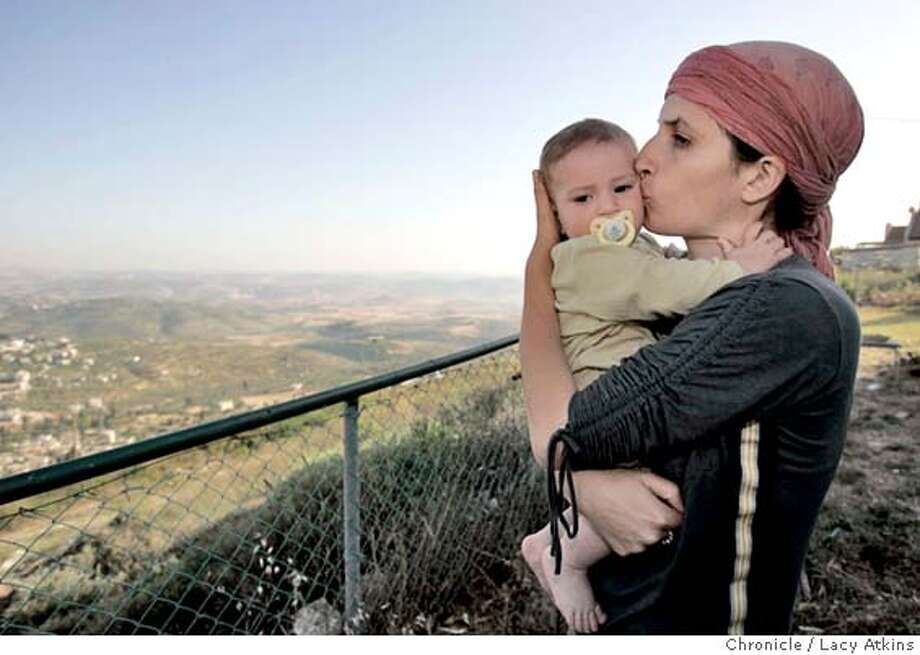 Menora Hazani kisses her baby as she looks towards the Palestinian village below her home in the Homesh Settlement in the West Bank, May 26, 2005. The Homesh Settlement is one of the four villages in the West Bank that will are part of the disengagement in August.  Photographer Lacy Atkins Photo: LACY ATKINS