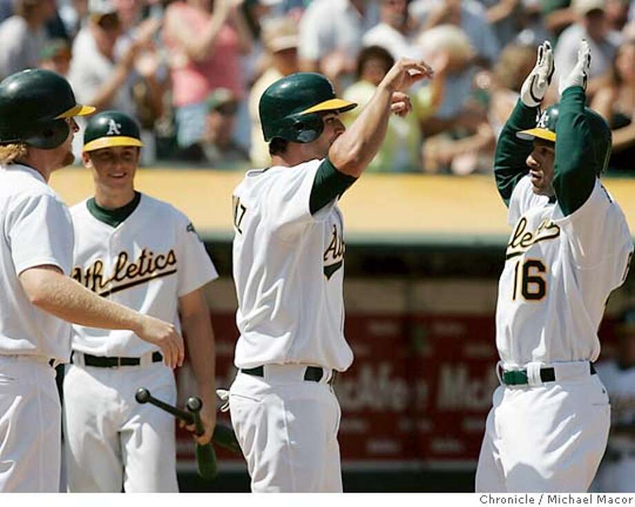 Athletic's 16- Jay Payton high fives 3- Eric chavez after his 3 run homer in the 6th to put Oakland up 4-2. Oakland Athletics vs. Minnesota Twins, Major League Baseball. 8/13/05 Oakland, Ca Michael Macor / San Francisco Chronicle Photo: Michael Macor