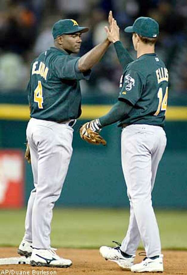 Oakland Athletics' Miguel Tejada (4) and Mark Ellis (14) high-five after their 3-1 win over the Detroit Tigers, Tuesday, May 13, 2003, in Detroit. Tejada's two-run double broke a seventh-inning tie for the win. (AP Photo/Duane Burleson) Photo: DUANE BURLESON
