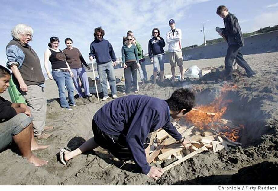 POTTERYFIRE_013_RAD.jpg SHOWN: Student in foreground adjusting the fire is Tao Kawase. The 10th grade pottery class at San Francisco Waldorf High School, under the direction of teacher Karen Apana (L, with white hair), fires their pottery projects, sculptures and vessels, in a traditional pit firing process on Ocean Beach. Karen Apana said this is one of the last permits for a pit fire to be issued by the GGNRA--as of April 1st there will be no more. For this pit firing, she needed a $1 million insurance policy from the school and a $55 permit fee. The beach is left cleaner than when the project begins. These pictures were made on Thursday, Feb. 15, 2007, in San Francisco, CA. (Katy Raddatz/SF Chronicle) **Karen Apana, Waldorf School, Tao Kawase Mandatory credit for the photographer and the San Francisco Chronicle. No sales; mags out. Photo: Katy Raddatz