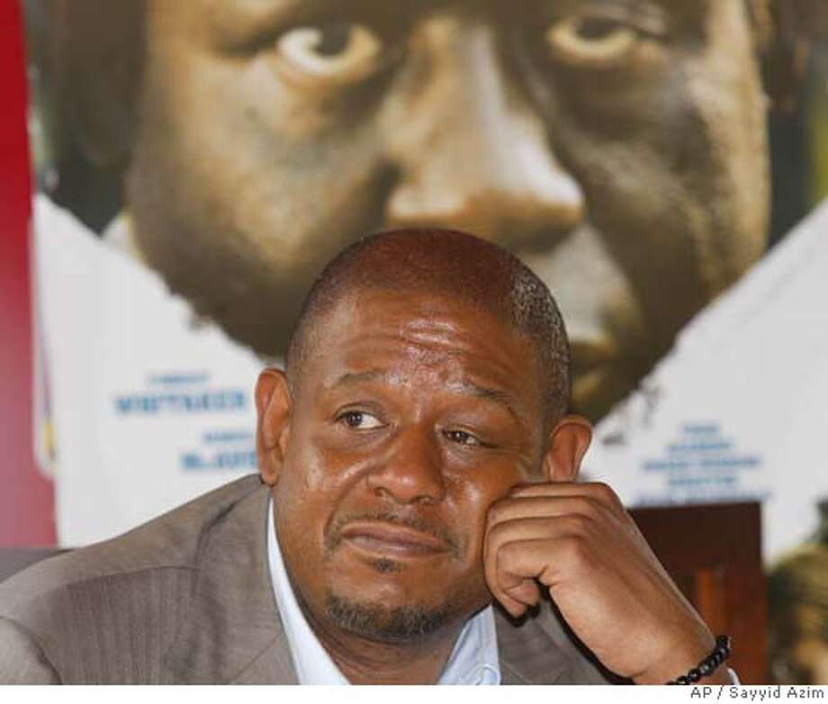Forest Whitaker poses in front of a large banner of the film The Last King of Scotland, as he answers questions from journalists in Kampala, Uganda, Saturday, Feb. 17, 2007. Kampala geared up for the premiere of award winning film The Last King of Scotland which portays the rule of Uganda's brutal dictator Idi Amin. The stars and director said they were deeply moved by the people of Uganda while filming the fictional account of one of the world's most brutal dictators and were happy to be back in the country for the Ugandan premiere of the film on Saturday night.(AP Photo/Sayyid Azim) Photo: SAYYID AZIM