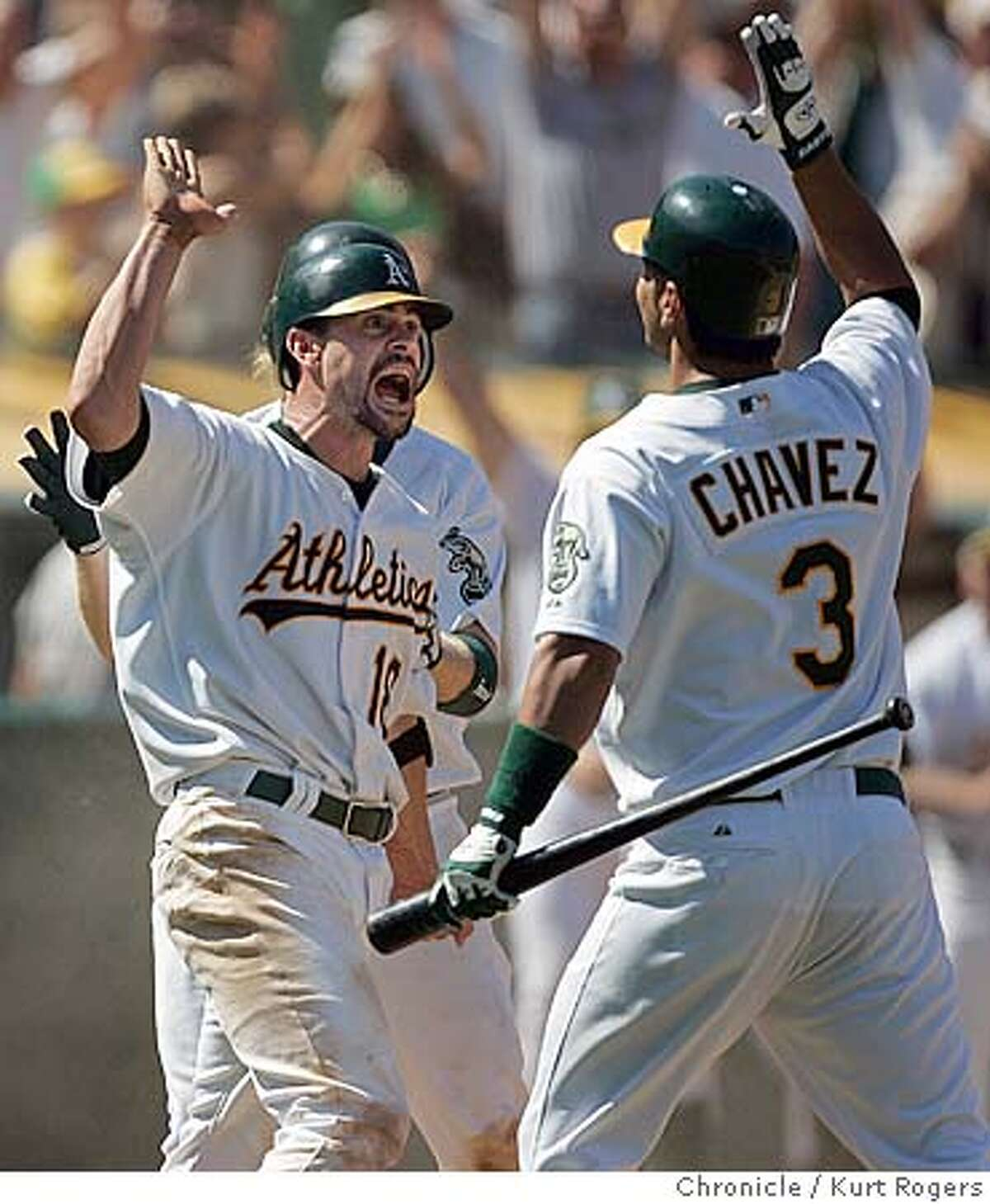 Jason Kendall after scoreing the winning run in the ninth high fives with Eric Chavez. Los Angeles Angels of Anaheim vs. Oakland Athletics . 8/11/05 in Oakland,CA. KURT ROGERS/THE CHRONICLE