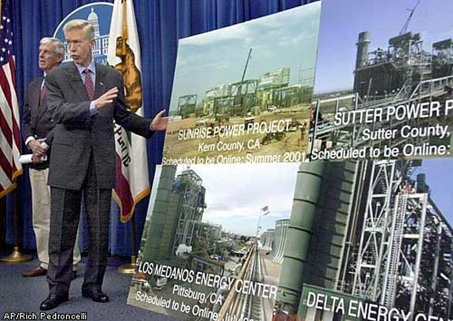 Gov. Gray Davis gestures towards a group of photographs showing the power plants that have been built since he became governor, during a news conference in Sacramento, Calif., Tuesday, May 13, 2003. Davis announced that he will ask the Public Utilites Commission to grant a $1 billion rate reduction for utility customers.(AP Photo/Rich Pedroncelli) Photo: RICH PEDRONCELLI