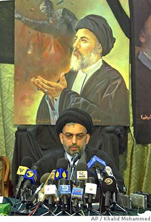 Abdel-Aziz al-Hakim, leading Shiite Muslim member of the Iraqi Governing Council holds a press conference in the holy city of Najaf, Iraq, Wednesday, Nov. 26, 2003. Al-Hakim said he discussed the Nov. 15 power-transfer accord on Tuesday with Grand Ayatollah Ali Husseini al-Sistani, Iraq's most influential Shiite leader. Painting in the background shows his brother Muhammed Baqir al-Hakim, who was killed in an explosion last August, and the falling statue of ousted Iraqi leader Saddam Hussein. (AP Photo/Khalid Mohammed) Iraqis look at a hole on the roof damaged by mortars in an overnight attack in central Baghdad. CAT Photo: KHALID MOHAMMED