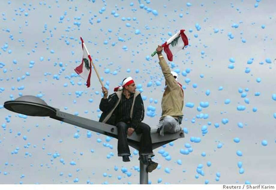 Lebanese supporters of assassinated Prime Minister Rafik al-Hariri wave flags as blue balloons fly over Martyrs Square during a mass rally in Beirut February 14, 2007. Lebanese supporters of assassinated Prime Minister Rafik al-Hariri wave a huge flag at Martyrs Square during a mass rally to mark the second anniversary of assassinated Prime Minister Rafik al-Hariri in central Beirut. REUTERS/ Sharif Karim (LEBANON) 0 Photo: SHARIF KARIM