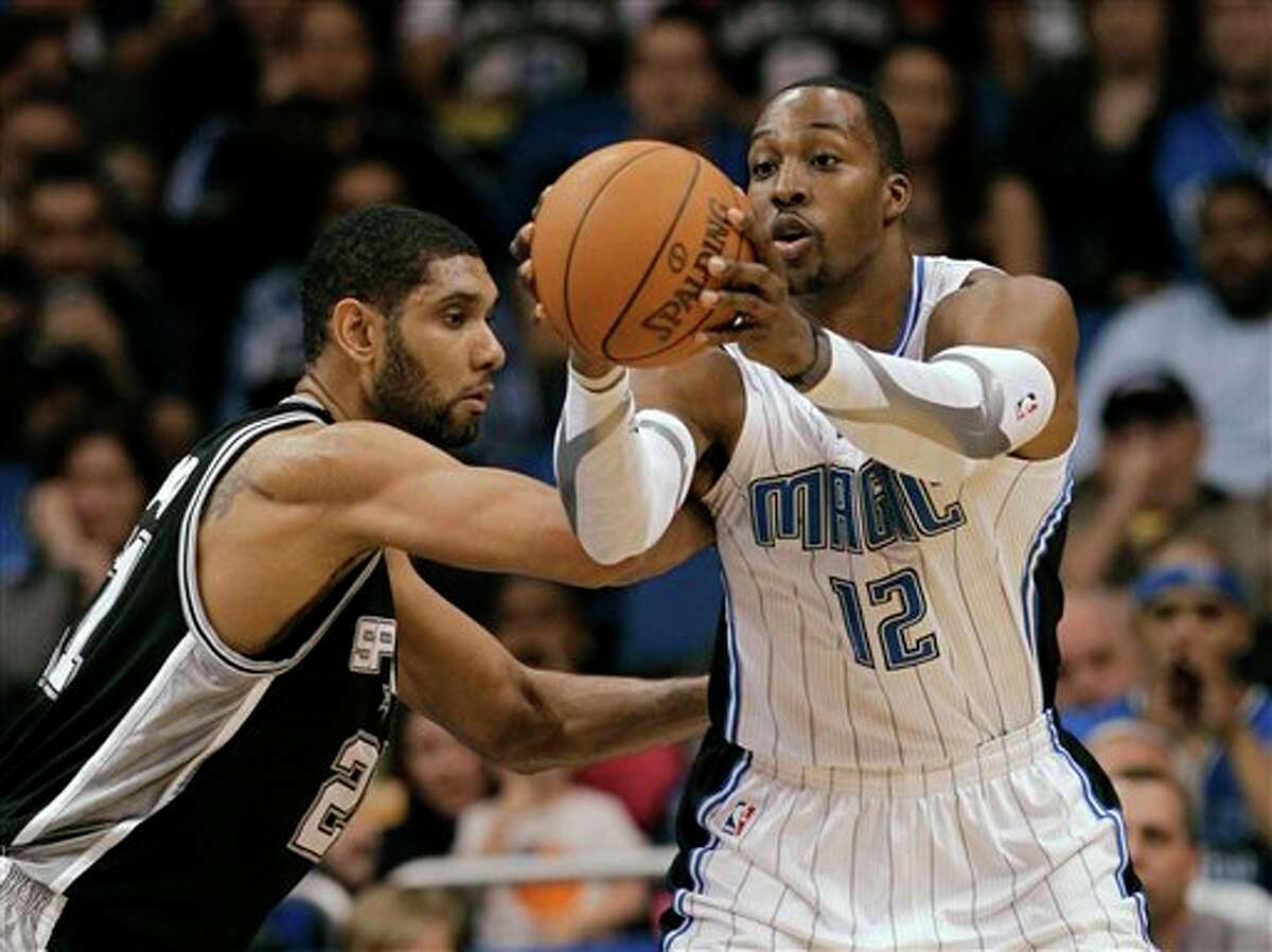 Orlando Magic center Dwight Howard (12) grabs a pass while being guarded by San Antonio Spurs' Tim Duncan during the first half of an NBA basketball game Wednesday, Jan. 18, 2012, in Orlando, Fla. (AP Photo/John Raoux)