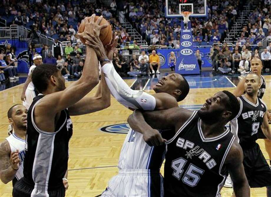 Orlando Magic's Dwight Howard, center, fights for a rebound with San Antonio Spurs' Tim Duncan, left, and DeJuan Blair (45) during the first half of an NBA basketball game Wednesday, Jan. 18, 2012, in Orlando, Fla. (AP Photo/John Raoux) Photo: Associated Press