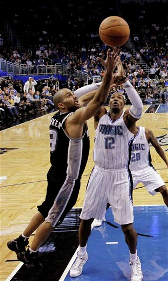 San Antonio Spurs' Tony Parker (9), of France, makes a shot over Orlando Magic's Dwight Howard (12) during the second half of an NBA basketball game Wednesday, Jan. 18, 2012, in Orlando, Fla. San Antonio won in overtime, 85-83. (AP Photo/John Raoux) Photo: Associated Press