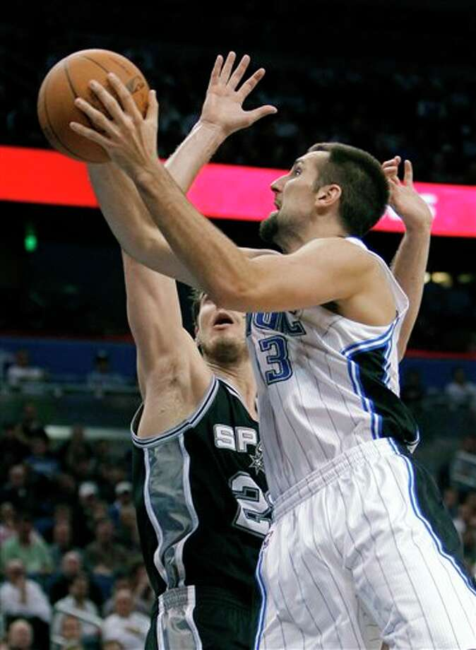 Orlando Magic's Ryan Anderson, right, makes a shot past San Antonio Spurs' Tiago Splitter, of Brazil, during the second half of an NBA basketball game Wednesday, Jan. 18, 2012, in Orlando, Fla. San Antonio won in overtime, 85-83.(AP Photo/John Raoux) Photo: Associated Press
