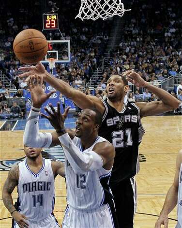 Orlando Magic's Dwight Howard (12) goes after a rebound in front of San Antonio Spurs' Tim Duncan (21) during the second half of an NBA basketball game Wednesday, Jan. 18, 2012, in Orlando, Fla. San Antonio won in overtime, 85-83. (AP Photo/John Raoux) Photo: Associated Press