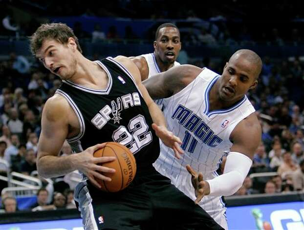 The Spurs' Tiago Splitter (left) spins away from Orlando's Glen Davis during the first half. Photo: Associated Press