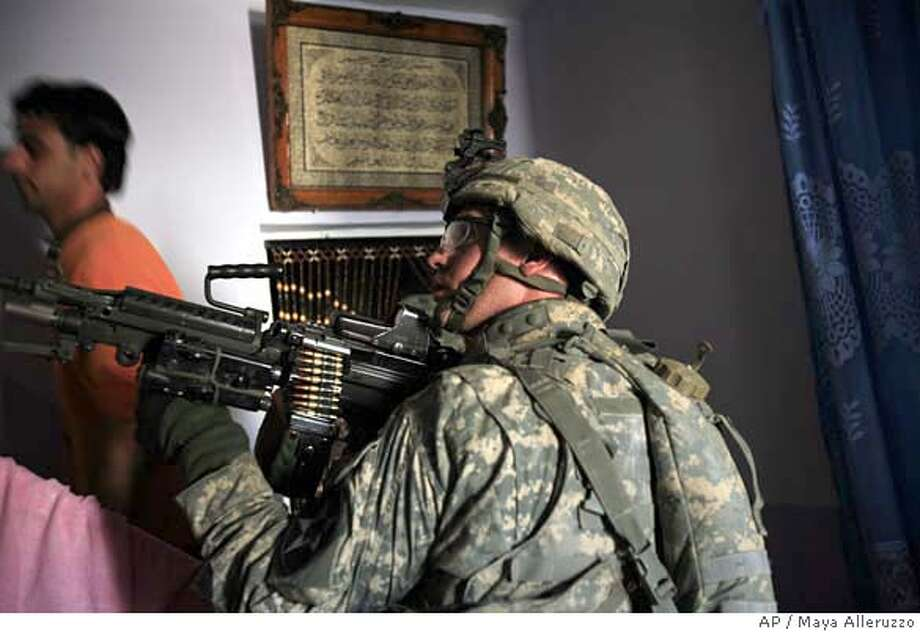 A US soldier from the 5th Battalion, 20th Infantry Regiment of the Second infantry Division searches a home in the Shaab neighborhood in Baghdad, Iraq Wednesday, Feb. 14, 2007. (AP Photo/Maya Alleruzzo) Photo: MAYA ALLERUZZO