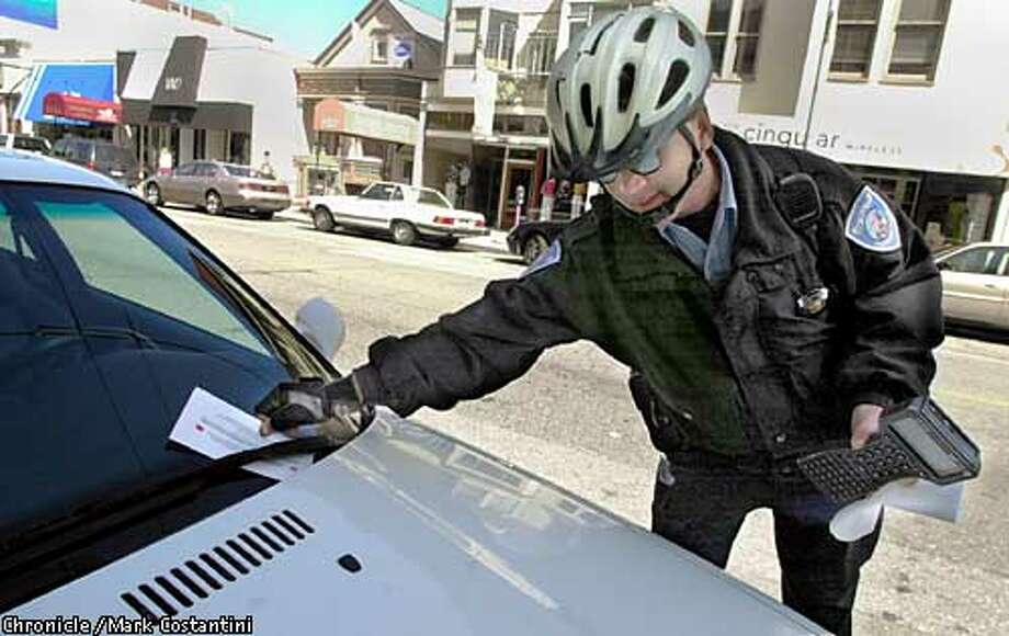 m&r12_0033_mc.jpg A S.F. parking enforcement officer who would not give his name tickets a BMW on Union Street. MARK COSTANTINI / The Chronicle Photo: MARK COSTANTINI