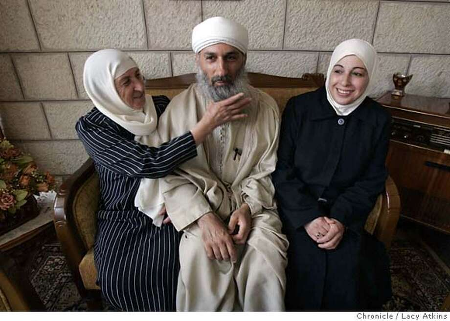 Suad Ma does the motherly thing with her son Sheikh Bassam Maraqa as she reaches to smooth out his beard while he sit for a photograph with his wife Nsreen at their home, Aug. 9, 2005, in Jerusalem Sheikh Bassam Maraqa�s full beard, hawk features, gleaming turban and flowing white robes make him a dead ringer for the notorious Osama bin Laden � a man Maraqa believes may be the Mahdi of prophecy, the messiah. He believes the Palestinians will fight for their own state, or for a shared state where they will soon be a majority; he fears that their hunger for peace will lead them to accept far less. But to Maraqa, the end game of Palestine is clear in the Koran: the day will come when Christianity allies with the Jews against Islam, which will triumph as the blood of the Jews fills pools in Jerusalem and the Mahdi returns. He is not the mainstream of Palestine � but he is a pole to which others are drawn.  Photo By Lacy Atkins Photo: LACY ATKINS