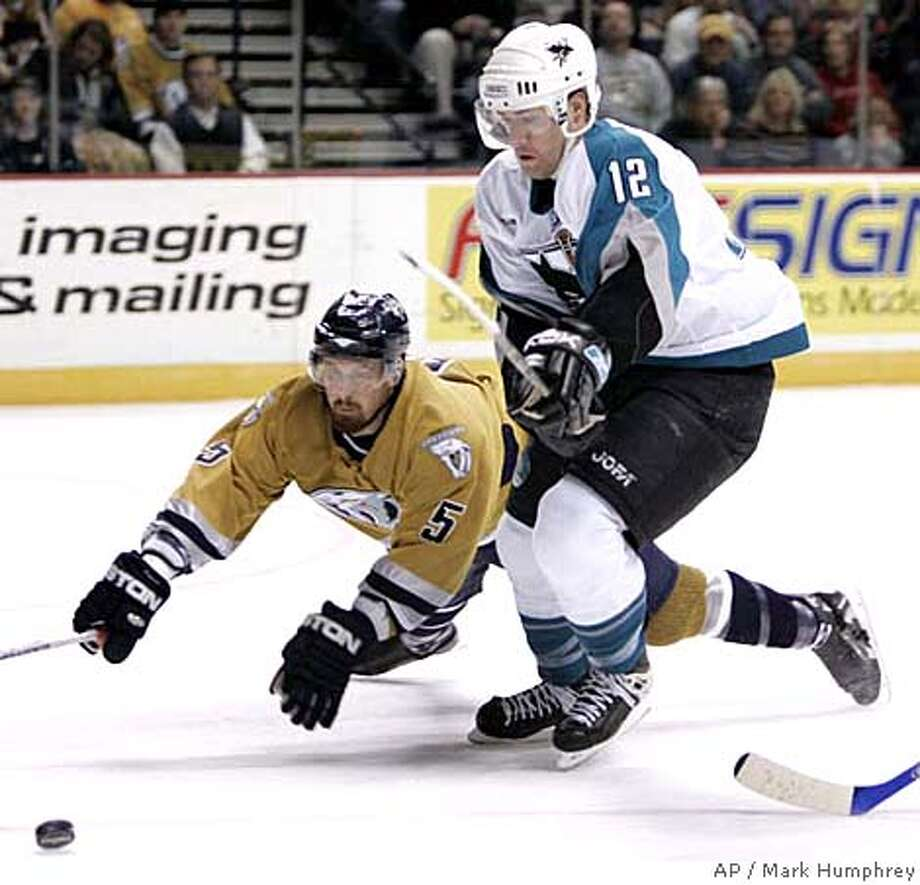 Nashville Predators defenseman Greg Zanon (5) dives to knock the puck away from San Jose Sharks center Patrick Marleau (12) in the second period of an NHL hockey game in Nashville, Tenn., Wednesday, Feb. 14, 2007. (AP Photo/Mark Humphrey) Photo: Mark Humphrey