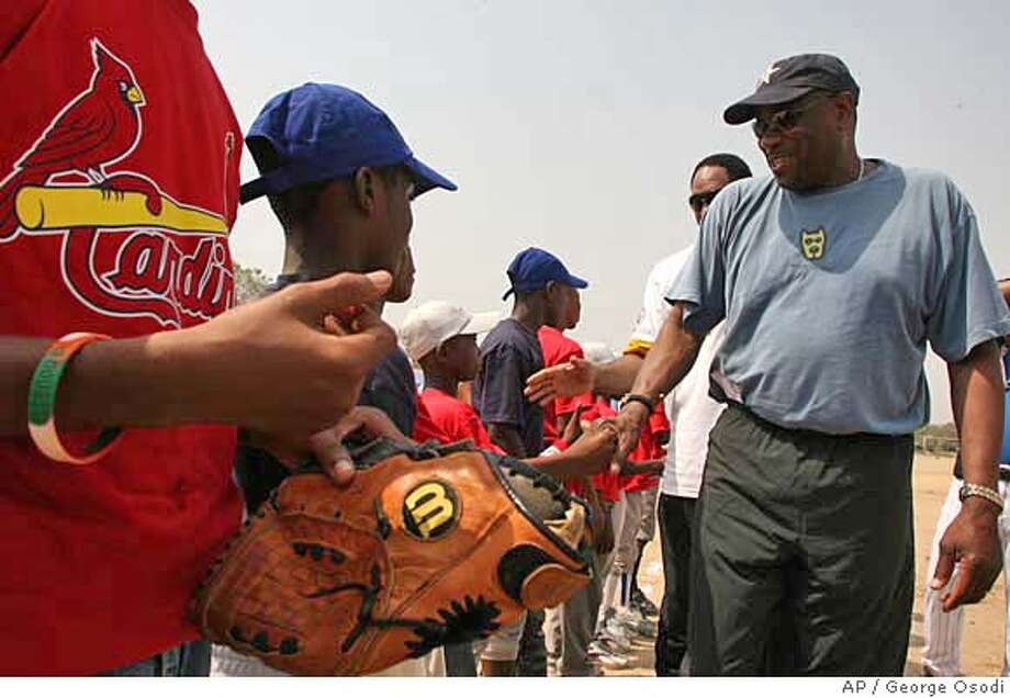 Former San Francisco Giants manager Dusty Baker, right shakes hands with a Ghana childrens baseball team in Tema about 30km from Accra, Ghana, Saturday, Feb. 3, 2007. A 22-member U.S Major League Baseball delegation are in the West African nation of Ghana on a goodwill trip aimed at promoting the sport in a region where little is known about it. (AP Photo/George Osodi) Photo: GEORGE OSODI