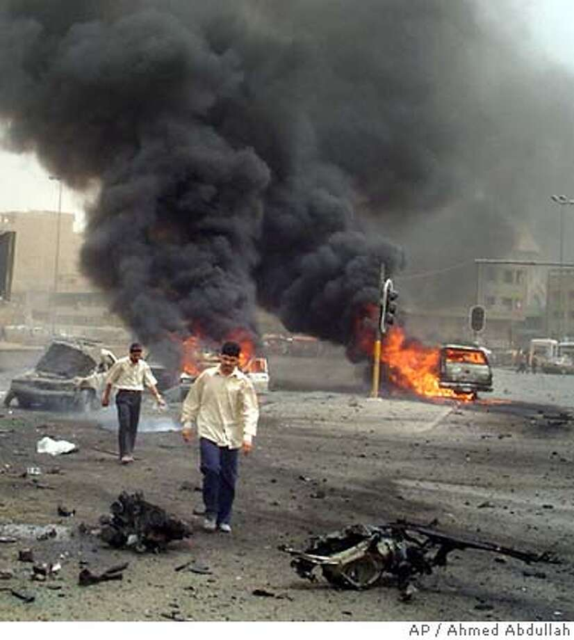 Onlookers walk away from the scene of a massive suicide car bomb explosion targeting a US military convoy, Tuesday, Aug. 9, 2005, in Baghdad, Iraq. Iraqi government officials say 5 civilians were killed with over 10 injured. It was not immediately known if there were any US military killed or wounded in the attack. (AP Photo/Ahmed Abdullah) Photo: AHMED ABDULLAH