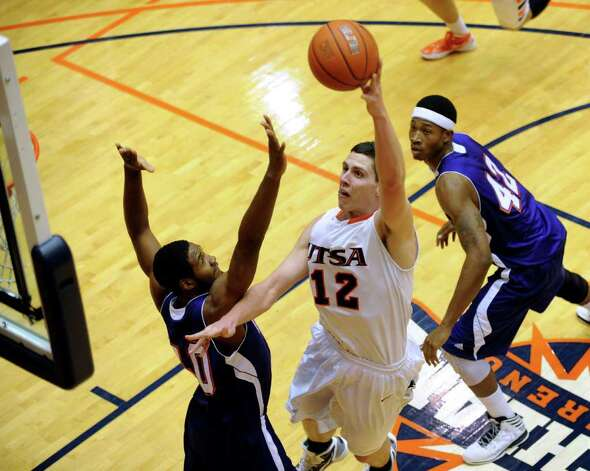UTSA forward Jeromie Hill shoots over Shamir Davis of Northwestern State during Southland Conference basketball action at the UTSA Convocation Center on Wednesday, Jan. 18, 2012. BILLY CALZADA / San Antonio Express-News 