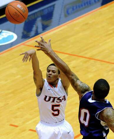 UTSA guard Michael Hale III makes a last-second shot to end the first-half as Shamir Davis of Northwestern State defends during Southland Conference basketball action at the UTSA Convocation Center on Wednesday, Jan. 18, 2012. BILLY CALZADA / San Antonio Express-News 