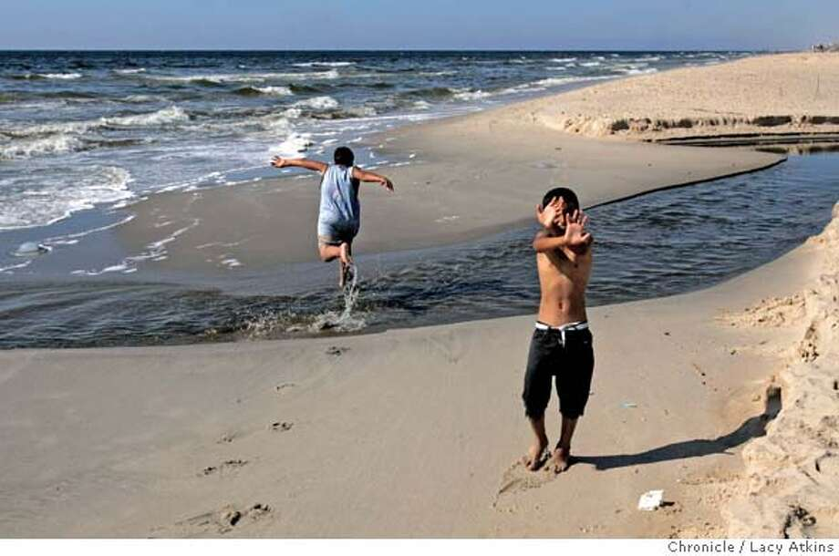 Children jump over the contaminated water as ehy plays along the beach, July 9, 2005, in Gaza of Israel. The sewage throughout Gaza is dumped across the coast road where it runs into the ocean. Photographer Lacy Atkins Photo: LACY ATKINS