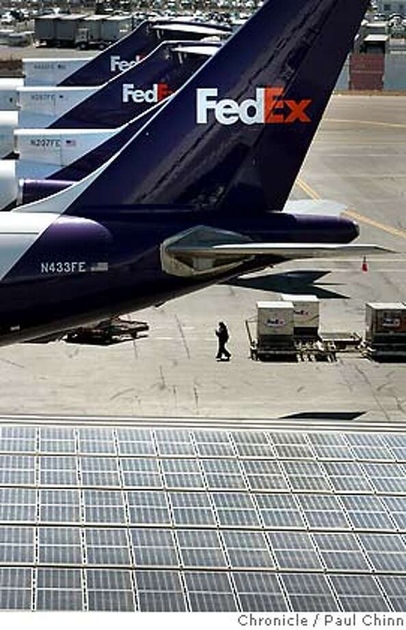 fedex09_120_pc.jpg  Solar panels stretch across a rooftop near a fleet of cargo jets at the FedEx west coast shipping hub on 8/2/05 in Oakland, Calif. The facility is set to flip the switch on the new energy system next week on Tuesday, August 9.  PAUL CHINN/The Chronicle MANDATORY CREDIT FOR PHOTOG AND S.F. CHRONICLE/ - MAGS OUT Photo: PAUL CHINN