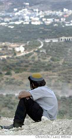 Avrahan (won't give last name) a settler from the Sa-Nur settlement looks out on to the Palestinian village below Sa-Nur, June 14, 2005, in the West Bank of Israel. Hundreds residents and supporters gather to Sa-Nur , in the West Bank for an anti-disengagement rally, June 14, 2005, in Israel. Twelve new families moved into the settlement during the rally. Sa-Nur is one of the four settlements that is scheduled to be removed in the disengagement in August. Photographer Lacy Atkins Hundreds residents and supporters gather to Sa-Nur , in the West Bank for an anti-disengagement rally, June 14, 2005, in Israel. Twelve new families moved into the settlement during the rally. Sa-Nur is one of the four settlements that is scheduled to be removed in the disengagement in August. Photographer Lacy Atkins Photo: LACY ATKINS