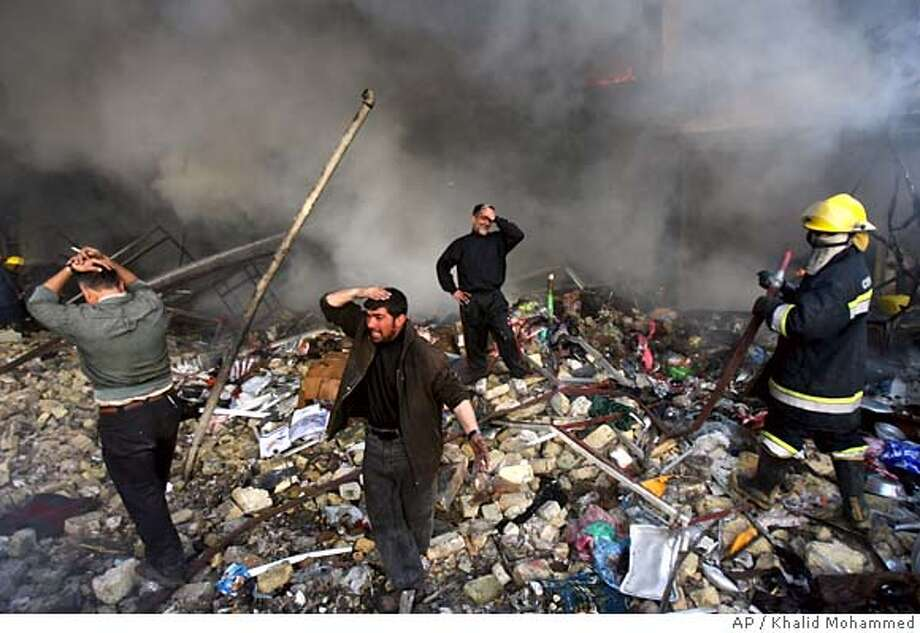 Iraqis grieve amid the rubble after a double car bomb attack in central Baghdad, Iraq, Monday, Feb. 12, 2007. Thunderous explosions and dense black smoke swirled through the center of Baghdad on Monday when at least one car bomb blew up in an underground parking garage, setting off dozens of secondary explosions and killing at least 59 people, police said. (AP Photo/Khalid Mohammed ) Photo: KHALID MOHAMMED