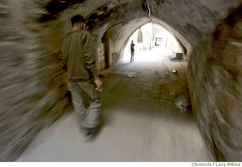 Jamil Haithem Faqha, leader of the Al-Aqsa Martyrs Brigade, walks through a tunnel in the Old City Market in Nablus of the West Bank, June 5, 2005. Photographer Lacy Atkins Photo: LACY ATKINS