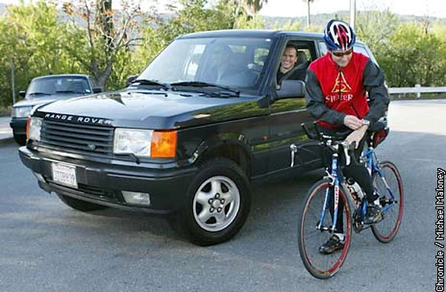 BIKE012_MJM.jpg  At the start of the race, cyclist Carl Guardino checks his watch as driver Marcus Liban looks on.  Bicycle races SUV to promote upcoming Bike to Work Day. 13-mile route from Los Gatos to San Jose. Bicyclist is Carl Guardino, president of Silicon Valley Manufacturing Group (a local trade assn.) SUV drivers are Marcus Liban and Dewey Yee, of SV Technology. Route goes from Guardino's house in Los Gatos to his office at 224 Airport Parkway, San Jose. City:� 5/9/03 in Los Gatos. MICHAEL MALONEY / The Chronicle Photo: MICHAEL MALONEY
