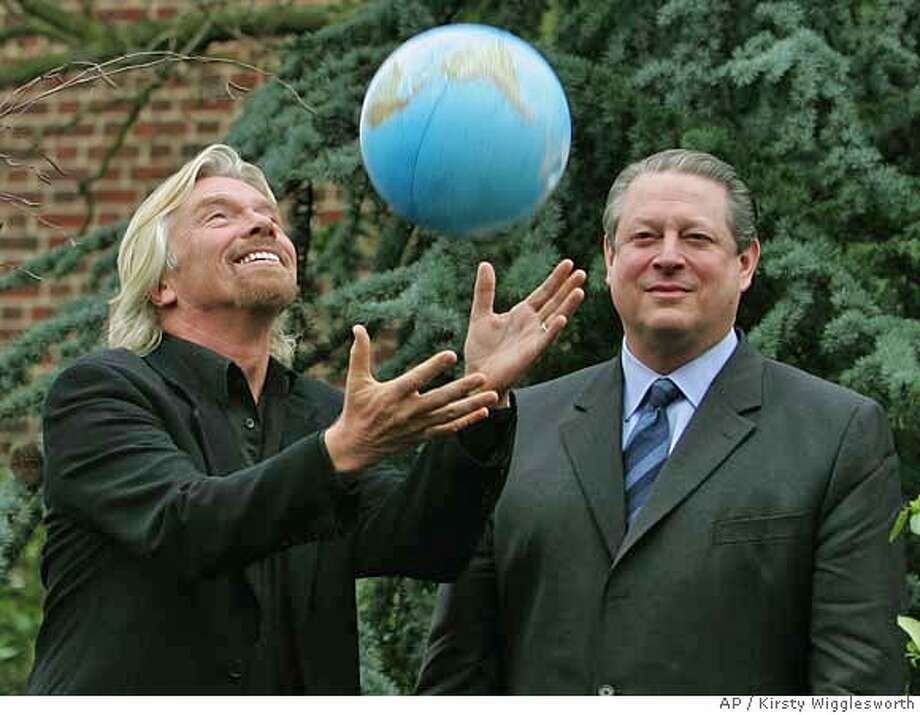 Sir Richard Branson , left, throws a globe into the air watched by former U.S. Vice President Al Gore, right, at a presentation to announce the Virgin Earth Challenge, in London, Friday Feb. 9, 2007. The Virgin Earth Challenge is a $25 million global science and technology prize, that will be awarded to an individual or a group who can demonstrate a design to reduce atmospheric pollution and contribute to the stability of the earth's climate. (AP Photo/Kirsty Wigglesworth) Photo: KIRSTY WIGGLESWORTH