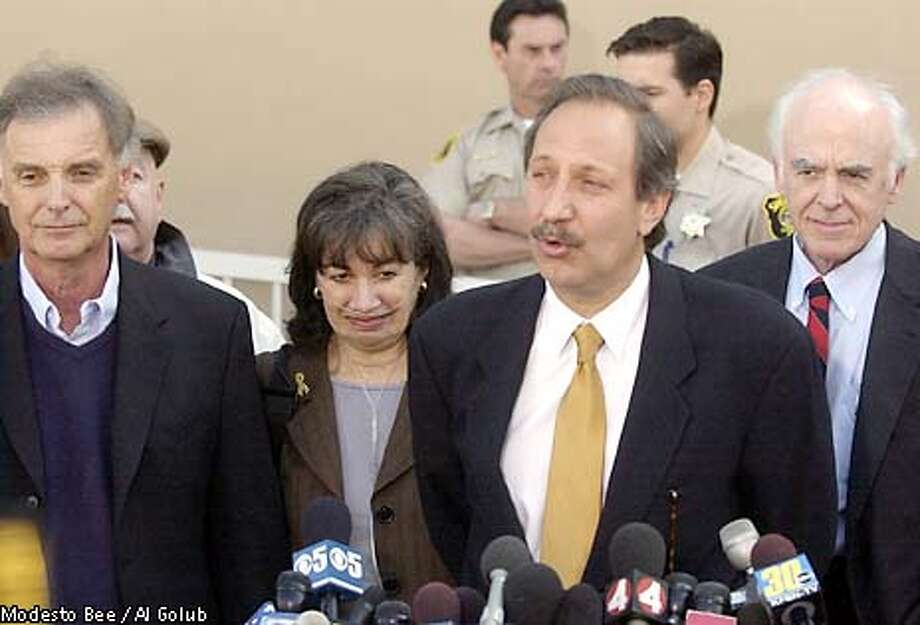 Defense attorney Mark Geragos, center, speaks to the media outside the Stanislaus Superior Court following a hearing, Friday, May 9, 2003, as Lee and Jackie , left, parents of Scott , listen with Modesto defense attorney Kirk McAlister, right, in Modesto, Calif. At the hearing a judge temporarily sealed more court documents in the double murder case after prosecutors said the investigation was ongoing and claimed that revealing evidence would jeopardize Scott 's chances of getting a fair trial. (AP Photo/Modesto Bee / Al Golub) Photo: AL GOLUB