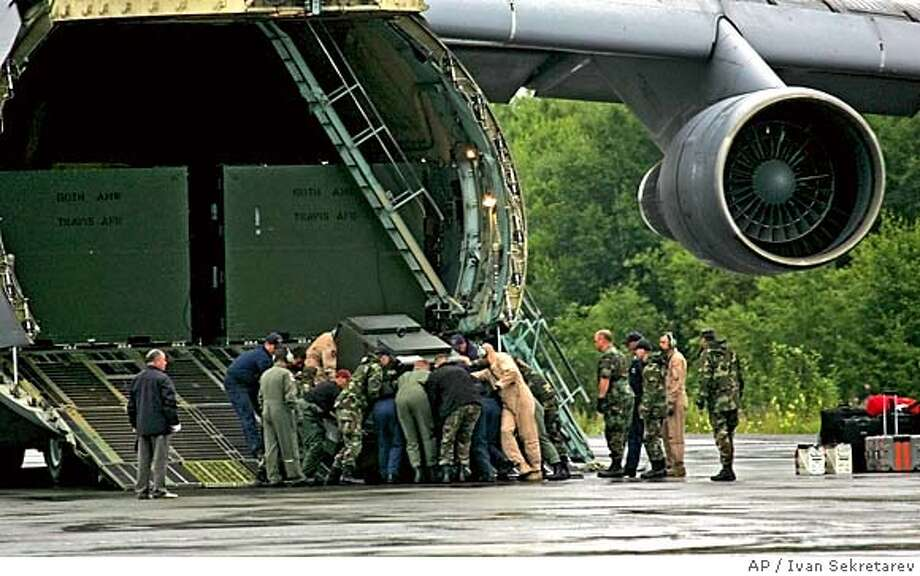 U.S. military personal unload a power generator from the USAF C-5 transport plane at the airport in Petropavlovsk-Kamchatsky, Russia Saturday, Aug. 6, 2005. The C-5 brought the Super Scorpio underwater robotic vehicle intended to help rescue the seven-man crew of a Russian mini-submarine trapped on the seabed off Kamchatka since Thursday. (AP Photo/Ivan Sekretarev) Photo: IVAN SEKRETAREV
