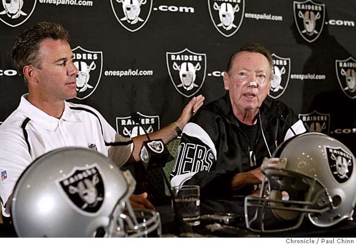 Oakland Raiders quarterback Rich Gannon pats owner Al Davis on the back after he announced his retirement during a news conference at Raiders training camp on 8/6/05 in Napa, Calif. PAUL CHINN/The Chronicle