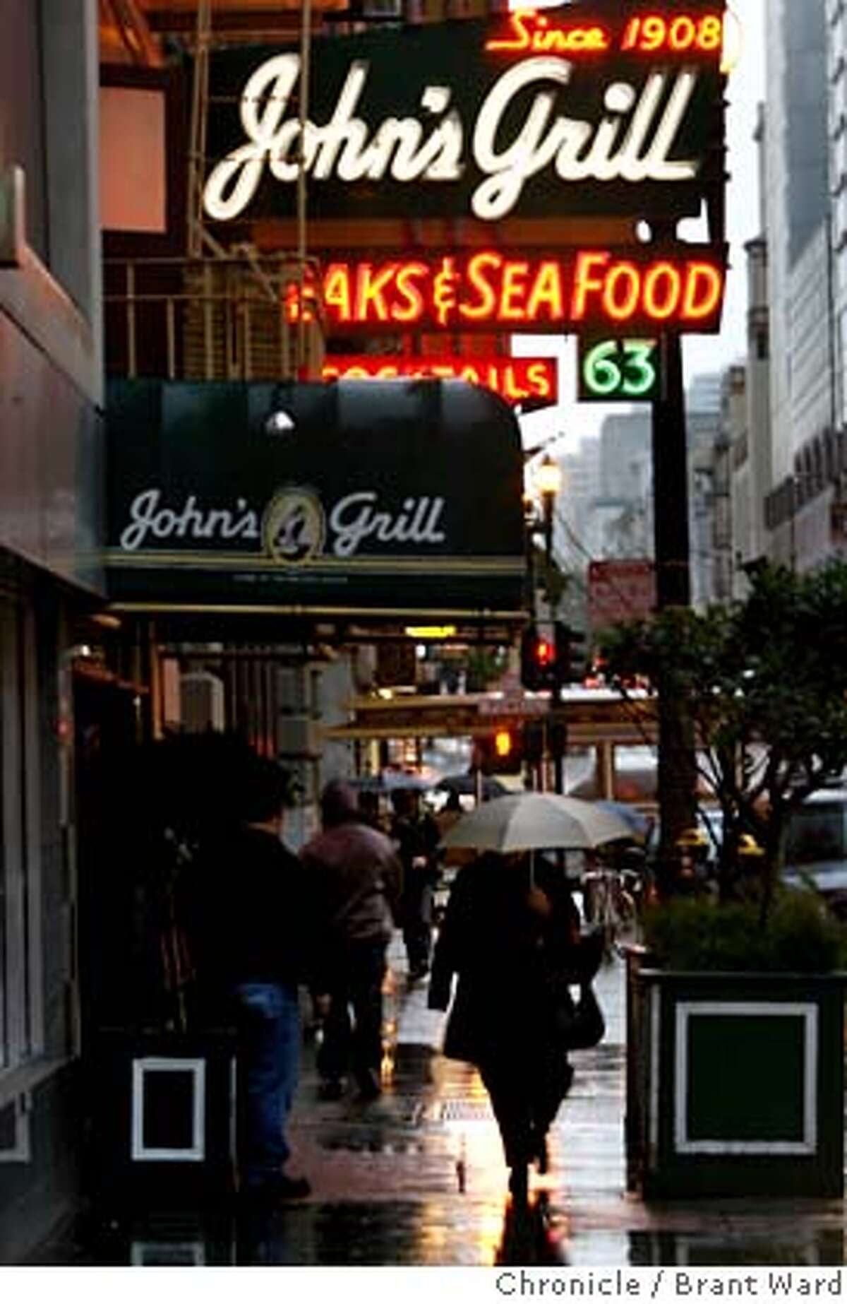 An early evening rain on Ellis Street as people hurried past John's Grill. A replica of the famous Maltese falcon used in the 1941 Humphrey Bogart film has been stolen from John's Grill restaurant in downtown San Francisco. {Brant Ward/San Francisco Chronicle}2/12/07