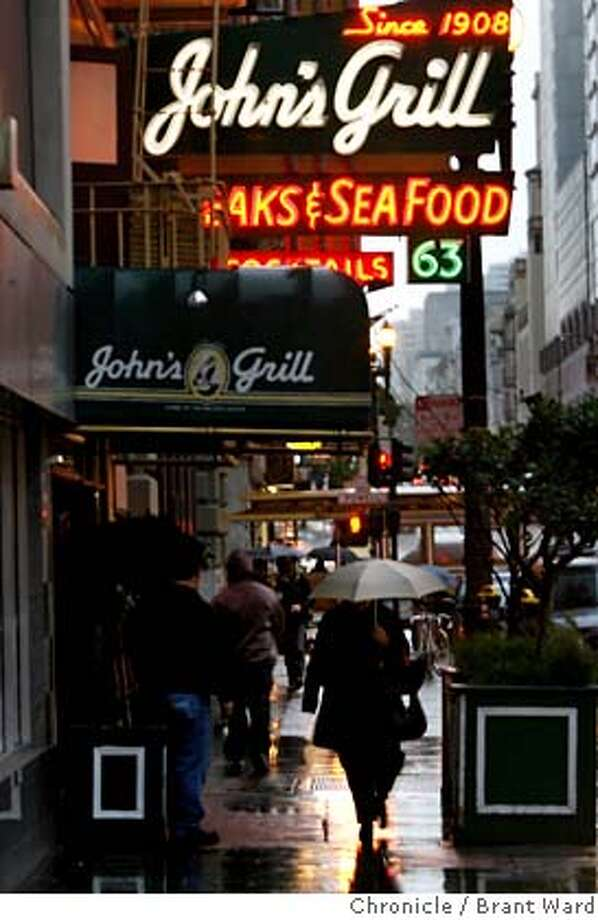An early evening rain on Ellis Street as people hurried past John's Grill.  A replica of the famous Maltese falcon used in the 1941 Humphrey Bogart film has been stolen from John's Grill restaurant in downtown San Francisco.  {Brant Ward/San Francisco Chronicle}2/12/07 Photo: Brant Ward