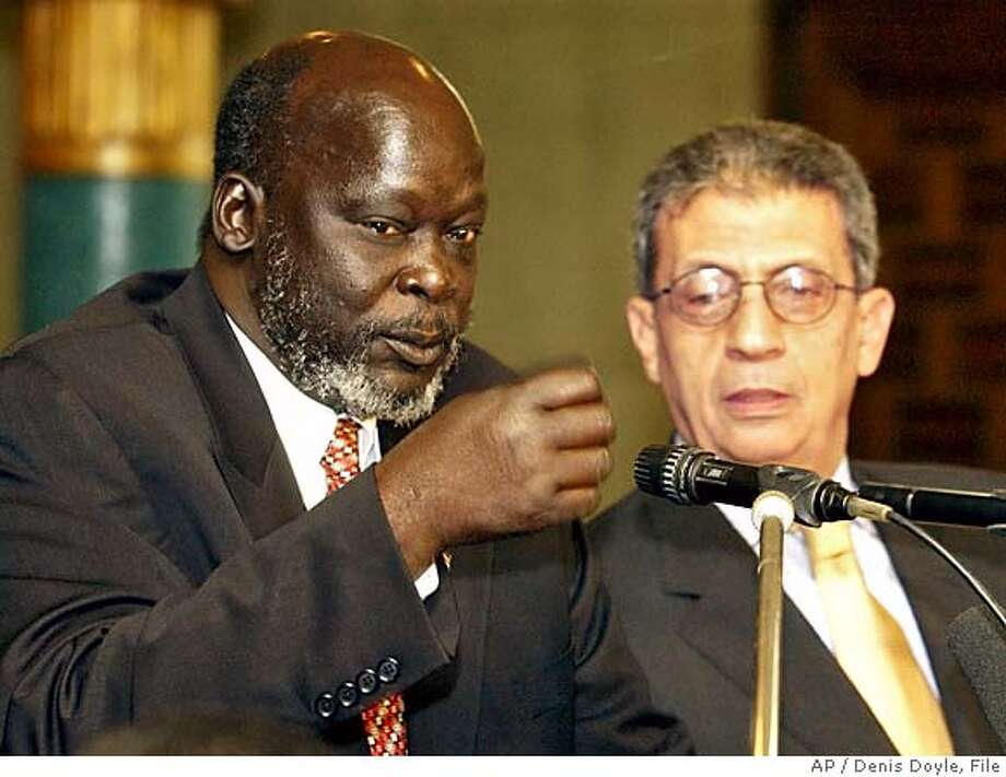 ** FILE ** John Garang, left, leader of the Sudanese southern rebels, makes a point as he sits next to Arab League Secretary General Amr Moussa during a joint press conference at the Arab League headquarters in Cairo April 7, 2003. Garang was found dead early Monday, Aug. 1, 2005, near the Uganda-Sudan border after the helicopter he was riding in crashed, a senior Ugandan official said. (AP Photo/Denis Doyle, File) Ran on: 08-07-2005  Pallbearers carry the coffin of John Garang, the first vice president of Sudan, to a cathedral. Photo: DENIS DOYLE