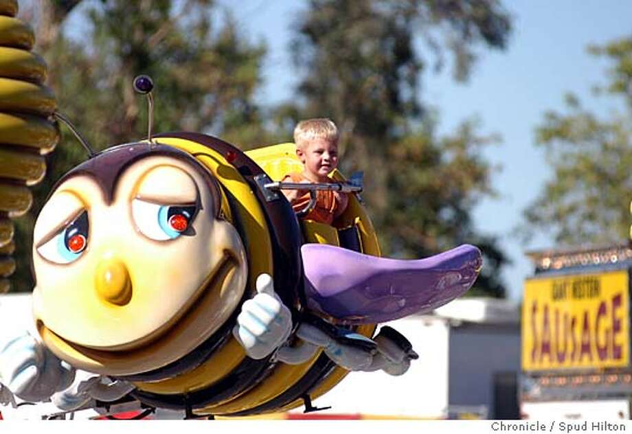 A youngster gets a friendly lift during one of the kiddie rides in the midway at the State Fair. Photos from the 2004 California State Fair to go with calwest story. Sacramento on 8/28/04.  Spud Hilton / The Chronicle Ran on: 08-07-2005  Don't worry, bee happy: A young rider gets a lift at the State Fair in Sacramento last year. Ran on: 08-07-2005 Photo: Spud Hilton